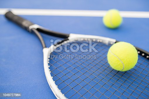 Sports background of yellow tennis ball  and racket laying on blue floor in court, copy space