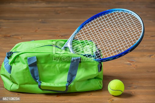 istock A tennis racket sticks out of a green sports bag, objects on the floor 682108234