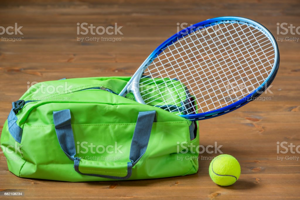 A tennis racket sticks out of a green sports bag, objects on the floor stock photo