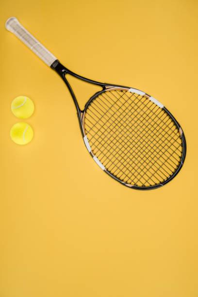 Tennis racket with balls isolated on yellow stock photo