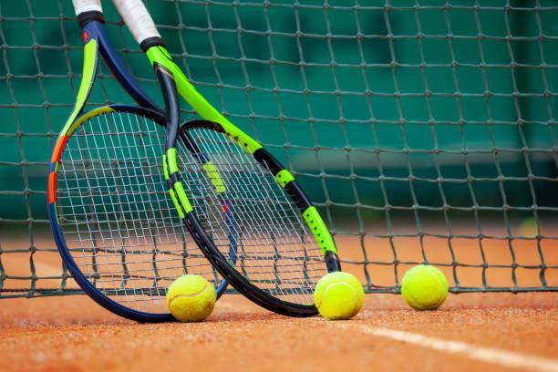 raquetas de tenis y pelotas apoyadas contra la red. - tenis fotografías e imágenes de stock