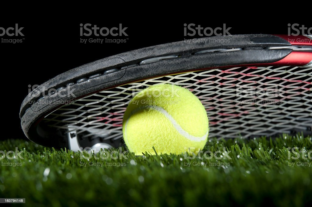 Tennis racquet and ball on the grass stock photo