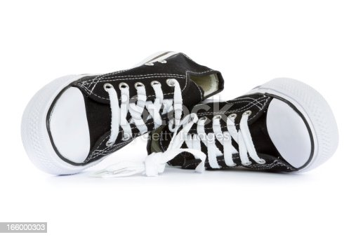 tied, brand new black and white tennis shoes on white background.