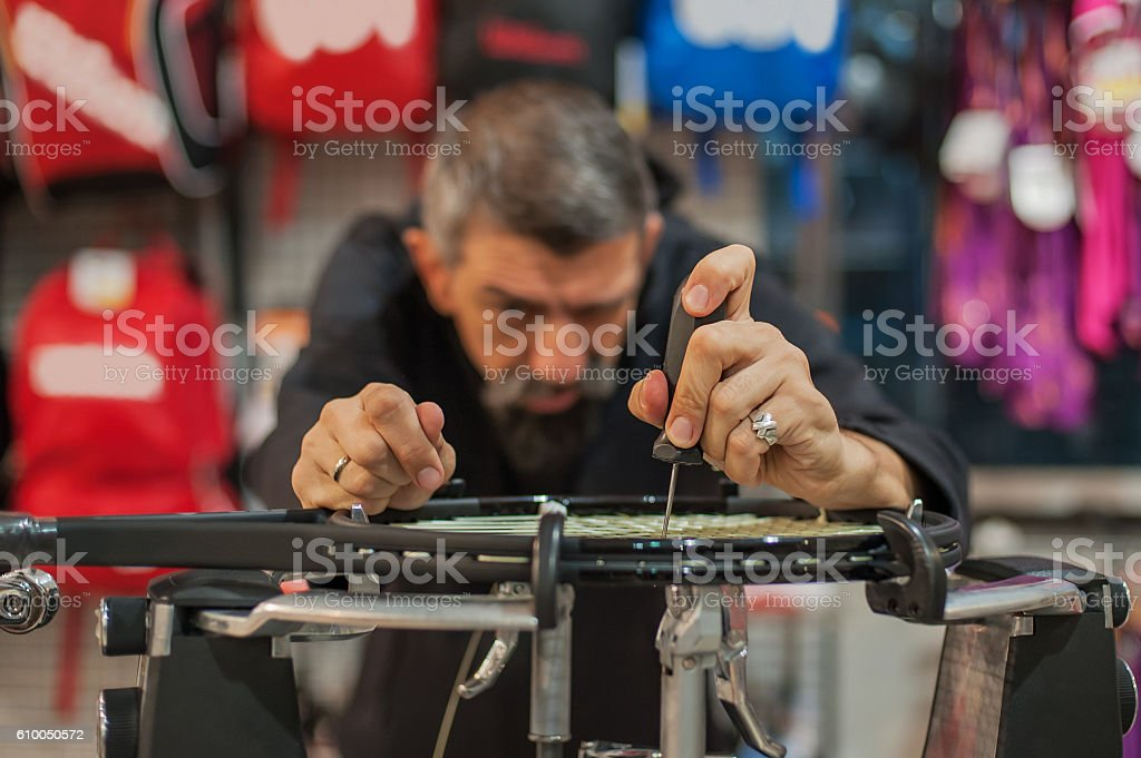 Tennis stringer holding awl and doing racket stringing stock photo