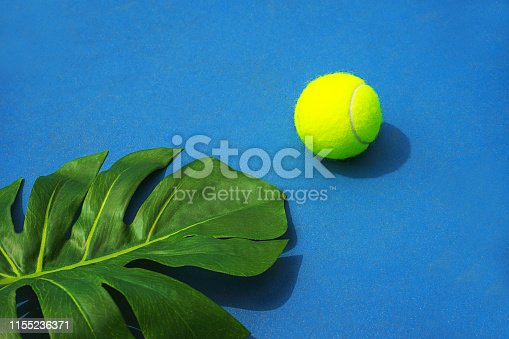 1153628111 istock photo Tennis summer concept with monstera leaf and tennis ball on hard court. 1155236371