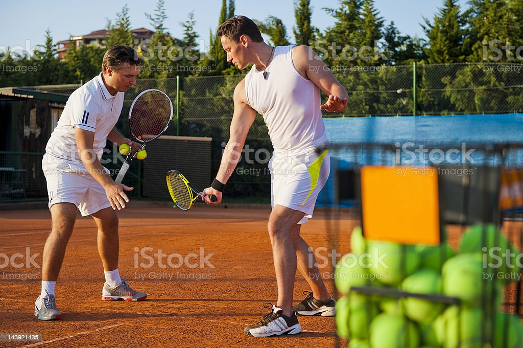 Tennis teacher giving lesson stock photo