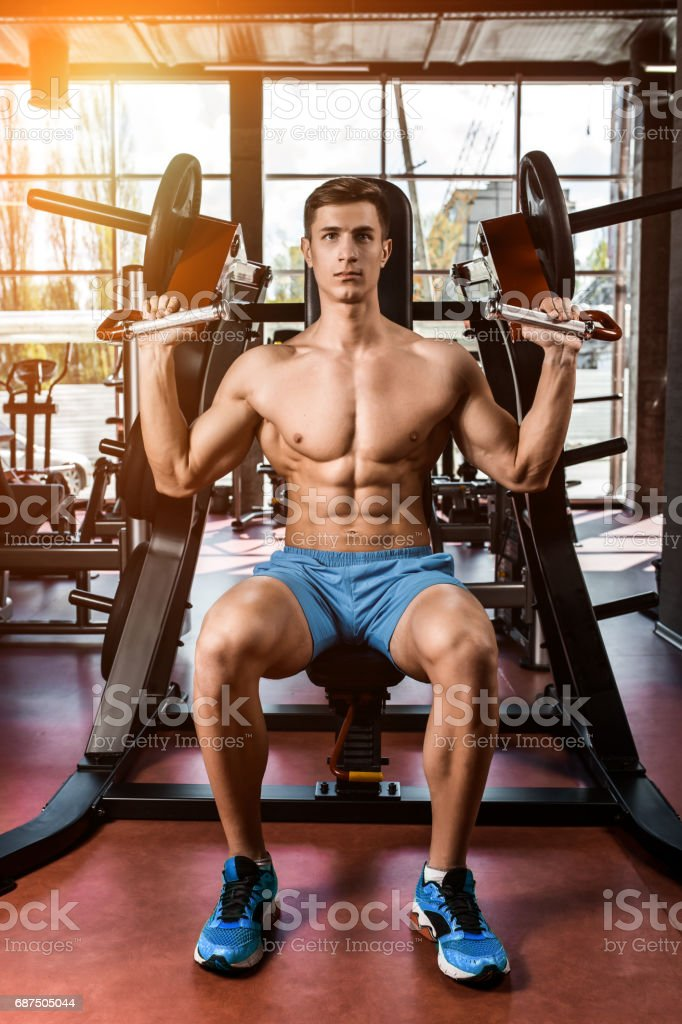 Tense muscles of hands under load. Man doing exercise for biceps in the gym stock photo
