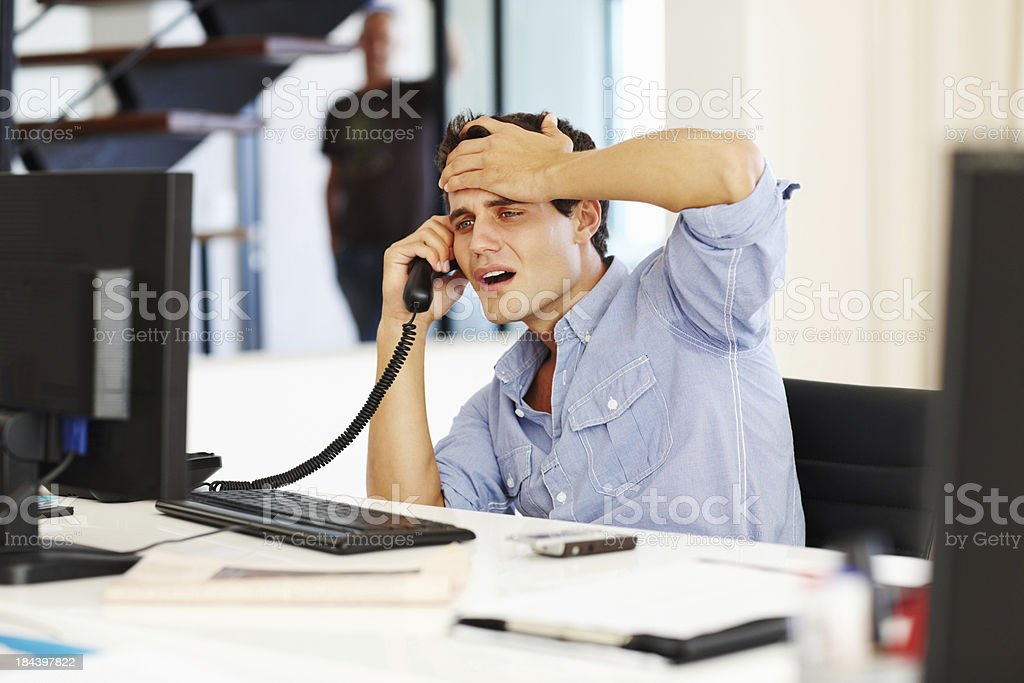 Tensed business man on call while looking at computer royalty-free stock photo