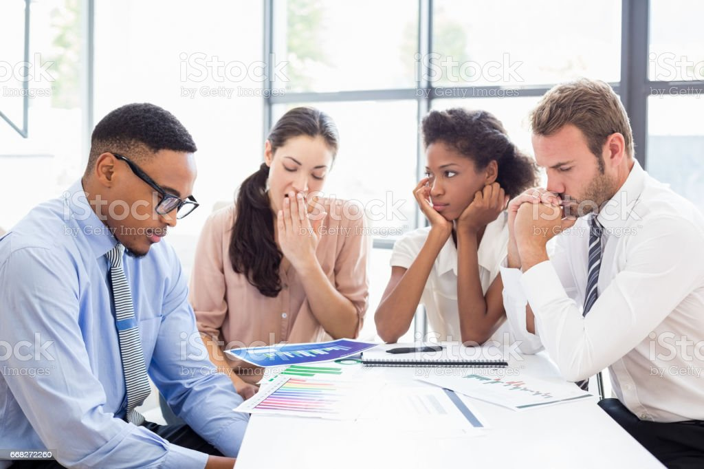 Tensed businesspeople sitting at table during a meeting stock photo