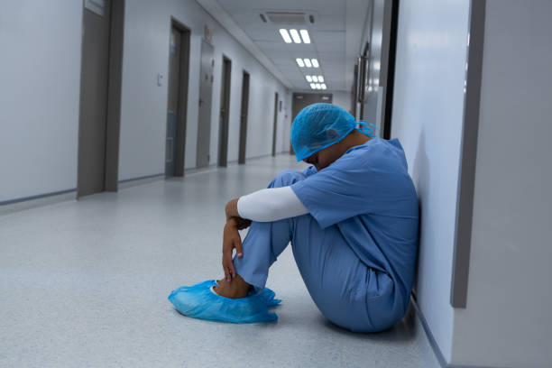 Tensed female surgeon sitting with eyes closed in the corridor stock photo