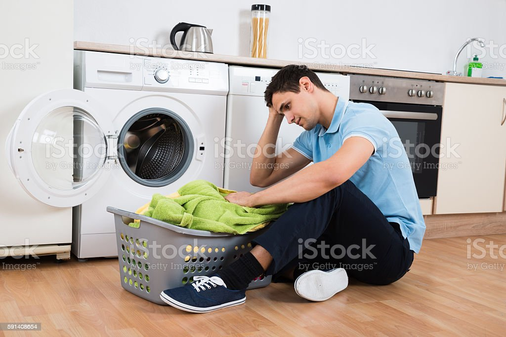 Tensed Man Looking At Laundry Basket By Washing Machine stock photo