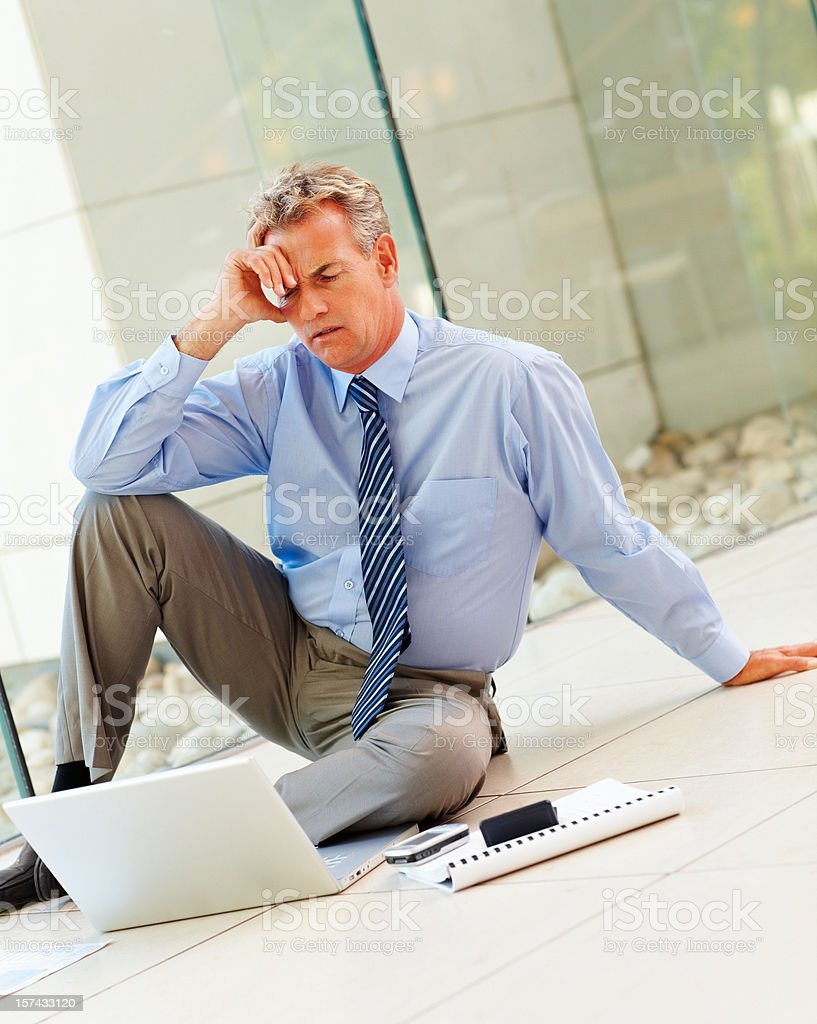 Tensed mature businessman looking at laptop royalty-free stock photo