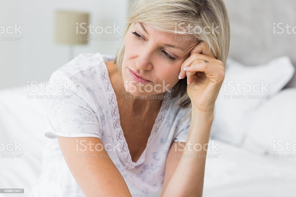 Tensed mature woman sitting in bed stock photo
