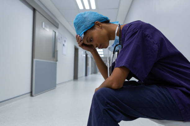 Tensed surgeon with hand on forehead sitting in corridor of the hospital stock photo