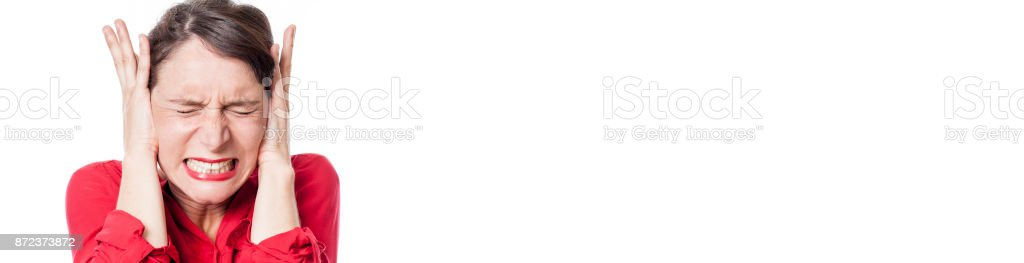 tensed young woman grinding teeth, covering her ears, long panorama stock photo