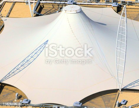 Temporary tensile structure on the top of a building - tensile structural design employs tensioned materials, whether they are textile membranes, light polymers or wire meshes, used primarily for the free roofing of large areas and are characterized by a low weight - modern architecture.