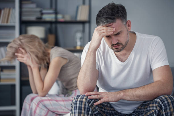 Tension between distant married couple Tension between a distant married couple with relationship problems with focus on the husband in the foreground erectile dysfunction stock pictures, royalty-free photos & images