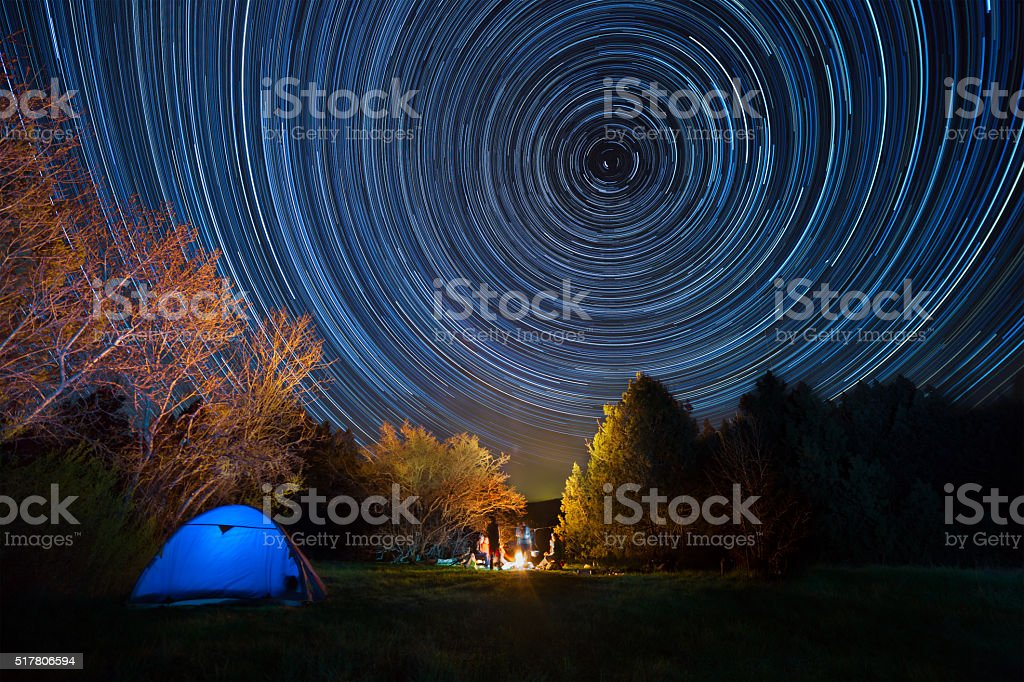 Tent against the night sky with tracks from stars stock photo