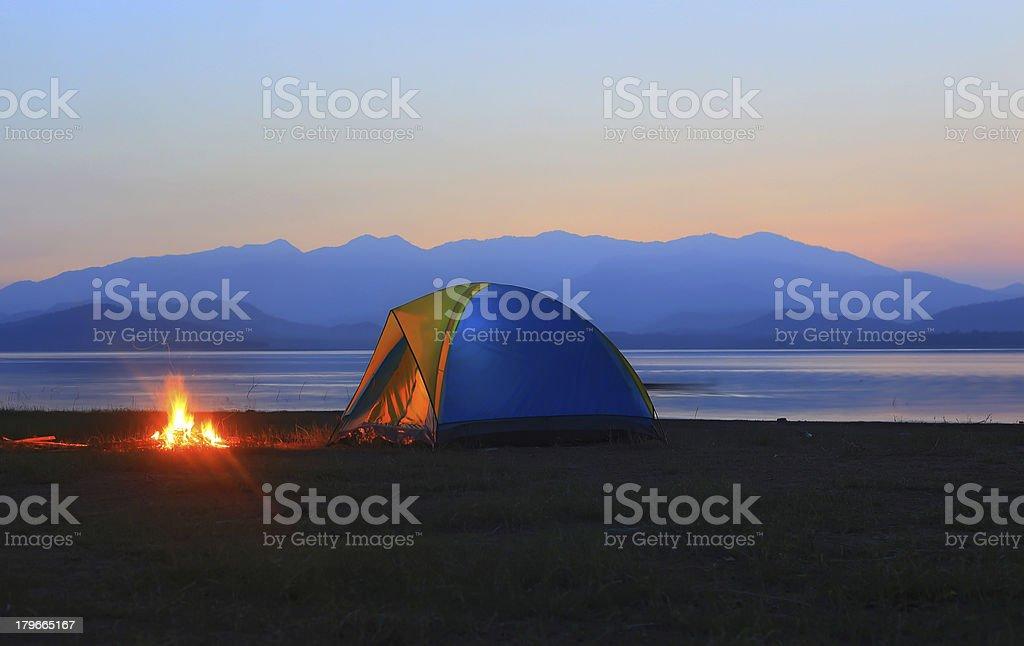 Zelt und Lagerfeuer bei Sonnenuntergang am See – Foto