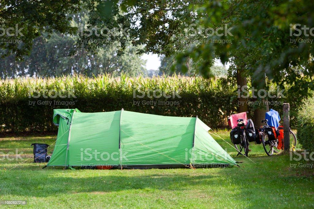 Tent en twee fietsen op een camping naast een maïsveld foto