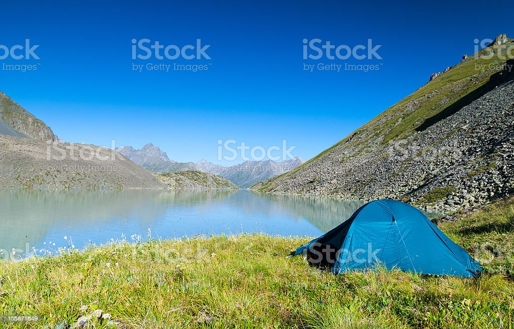 Tent at the shore of mountain lake stock photo