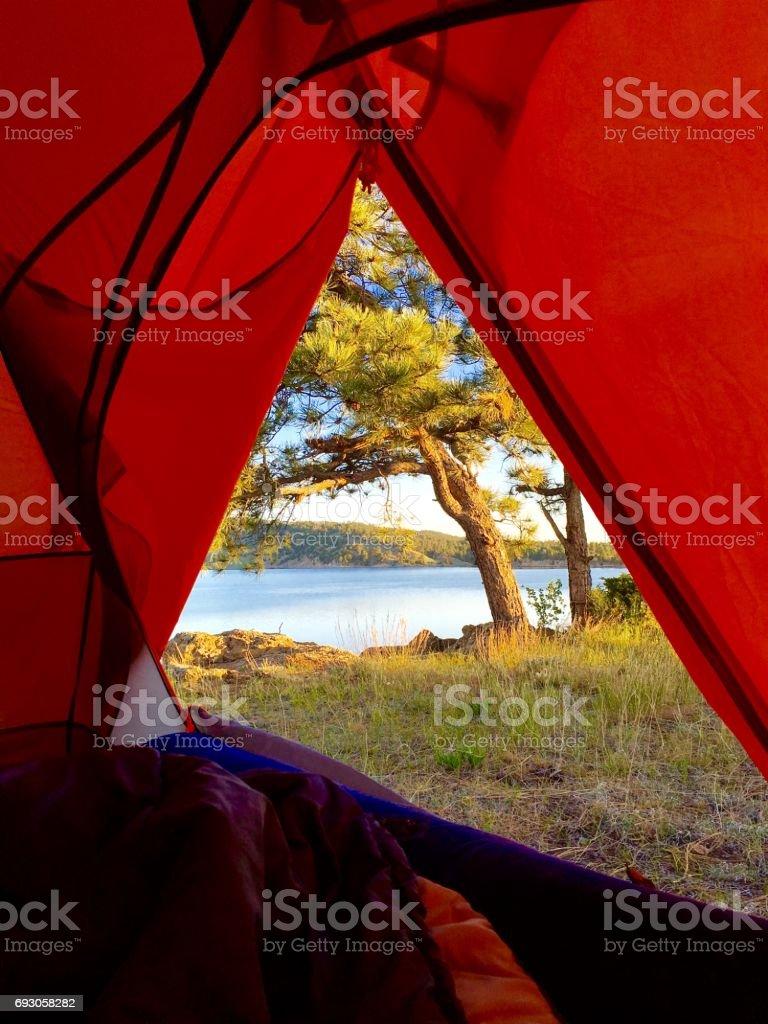 tent door camping and overlooking lake stock photo