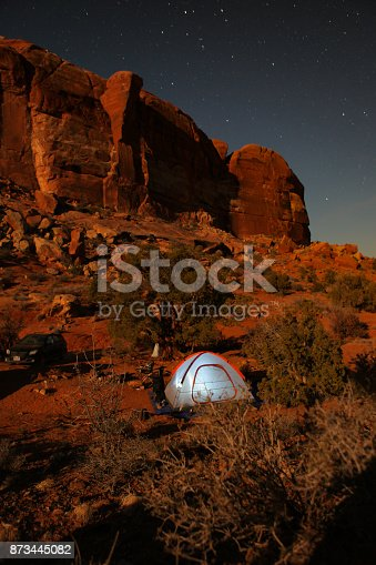 Moonlit cliffs and starry sky with a tent camping below.