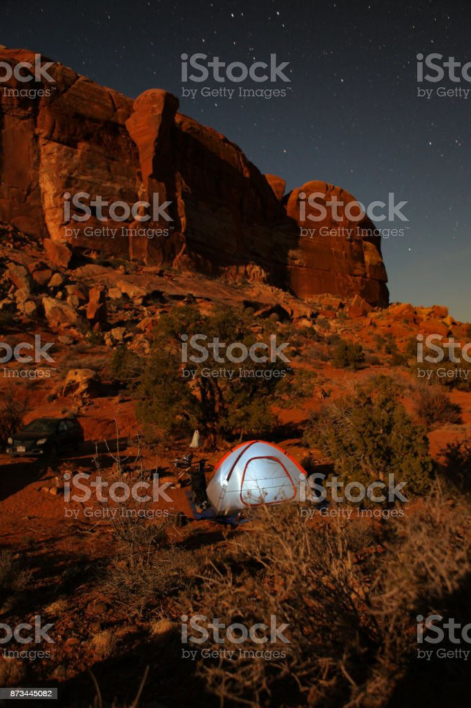tent glows under a night sky in moab stock photo