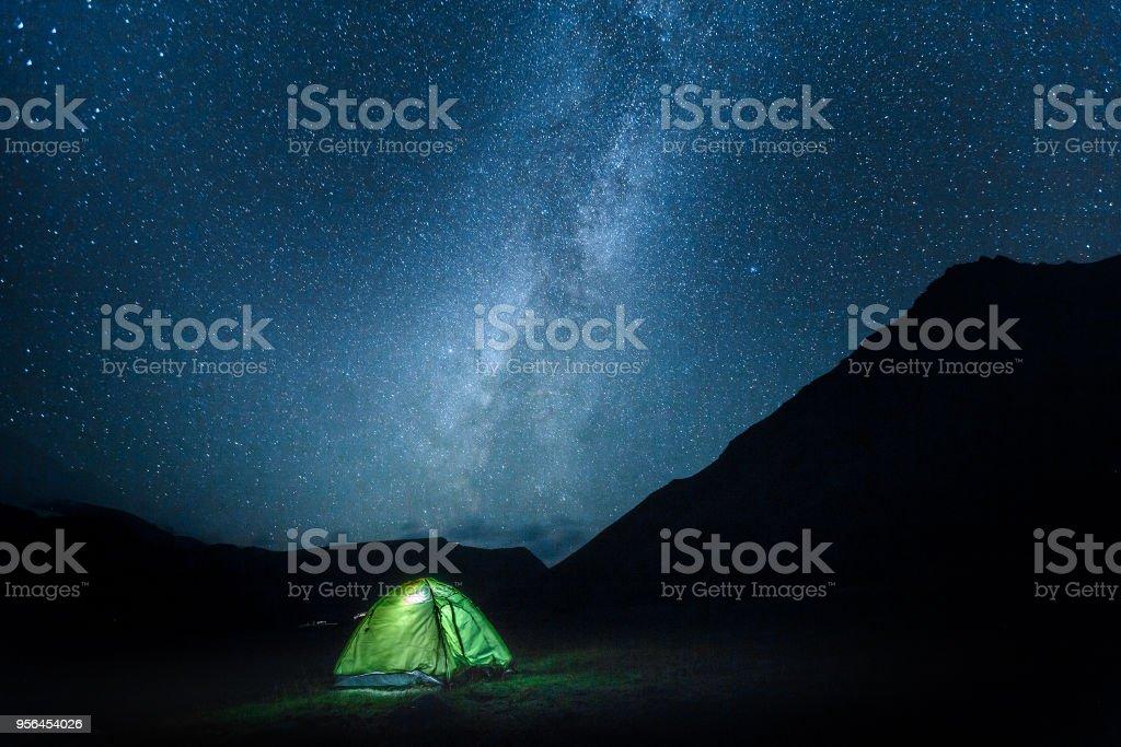 Green tent glows under a night sky Milky May full of stars. Elbrus...