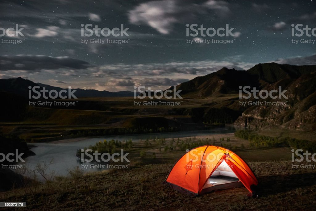 A tent glows under a night sky stock photo