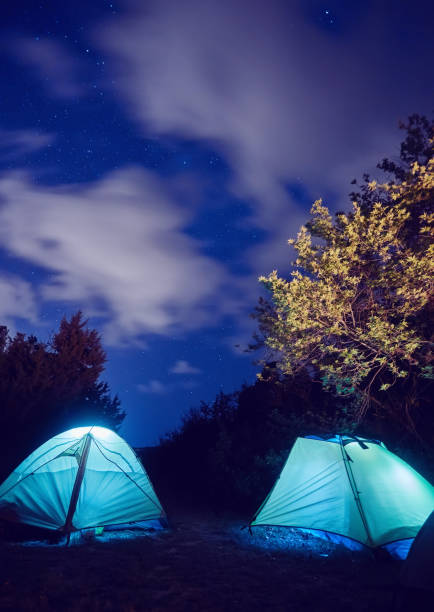 tent in the mountains under a starry sky stock photo