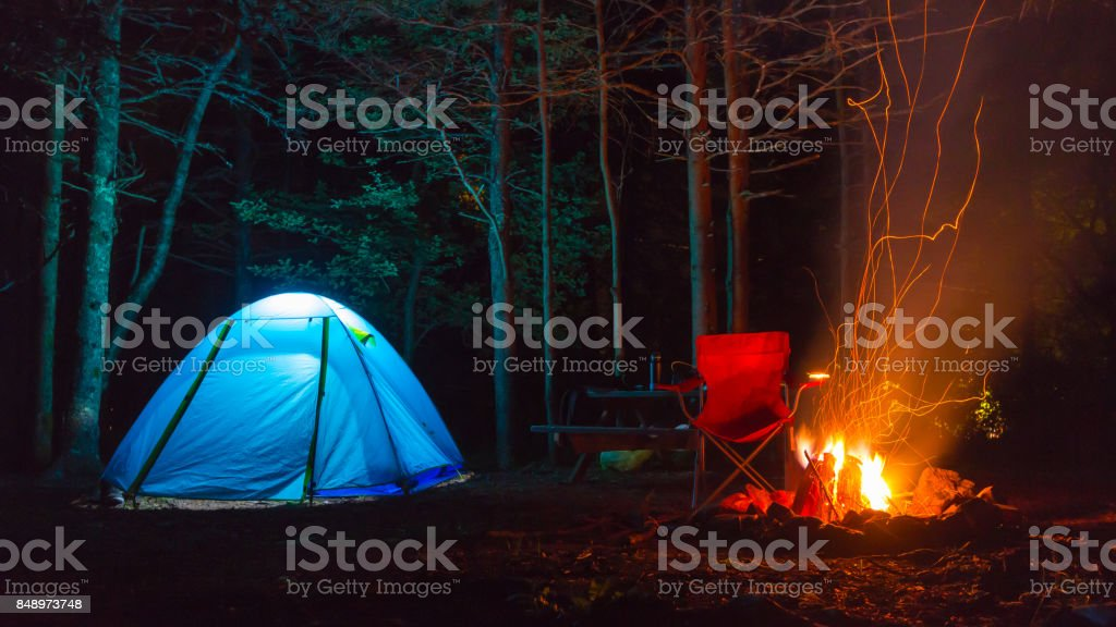 Tent lit up at night with fire pit stock photo