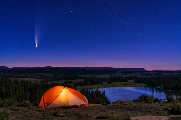Tent Lit Up with NEOWISE Comet in Sky stock photo