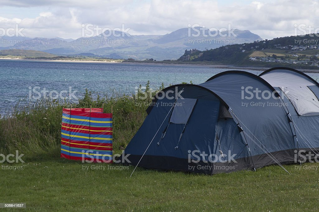 Tent looking over Harlech Castle and Snowdon. stock photo