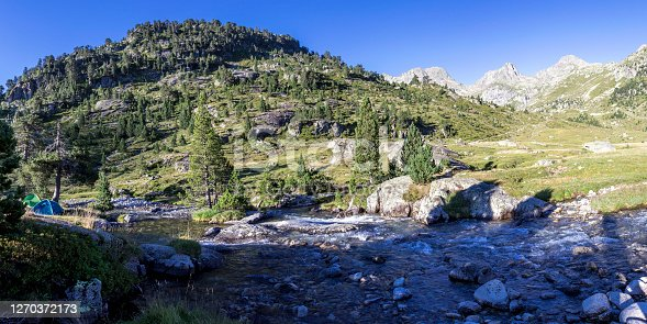 Camping site with tent next to glacial river in mountain landscape near refuge Wallon Marcadau located in beautiful valley in French Pyrenees, on High Pyrenean Route, France, Europe
