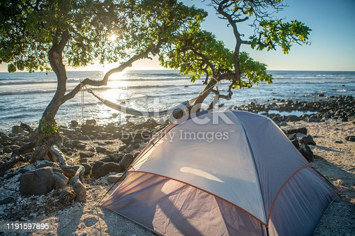 istock Tent on the beach at sunset, hammock hanging on trees, no people 1191597895