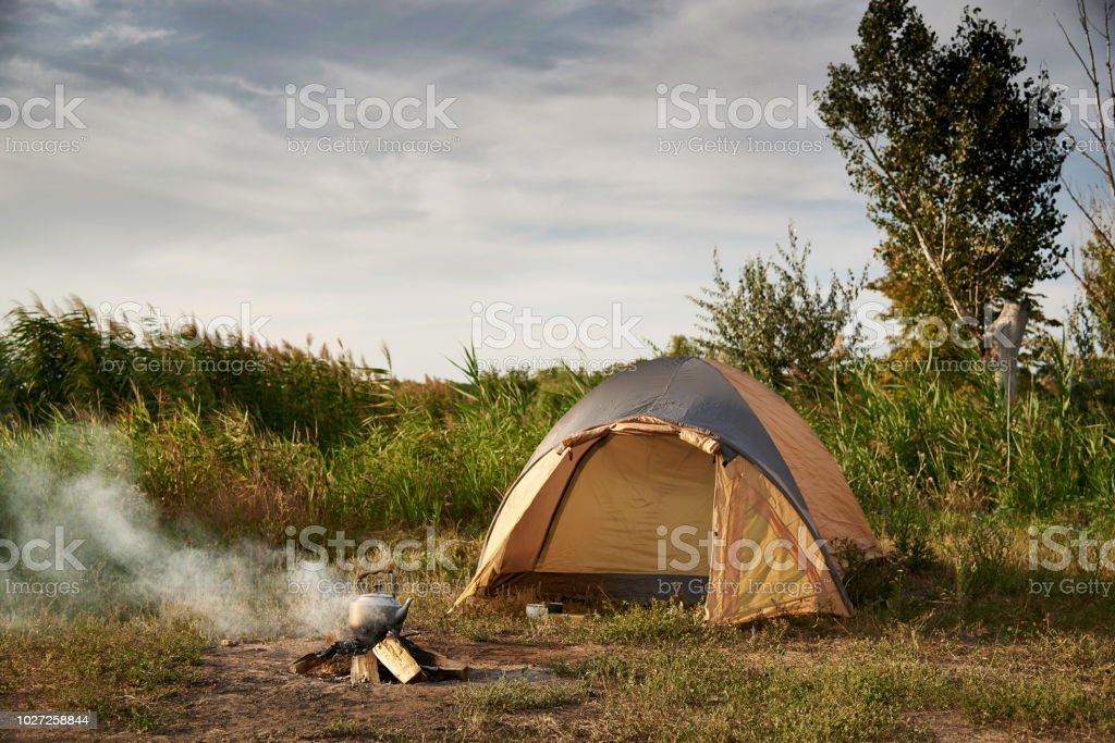 Tent on the shore of the lake near a burning fire with a kettle. stock photo