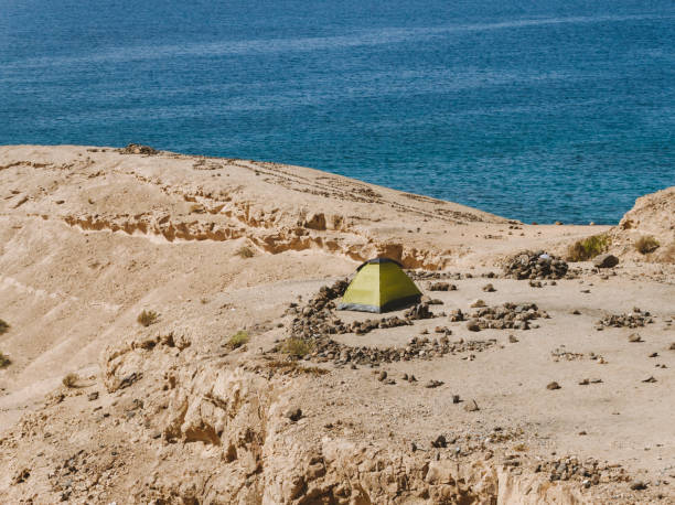 Tent on the top of the sand hill near water - fotografia de stock