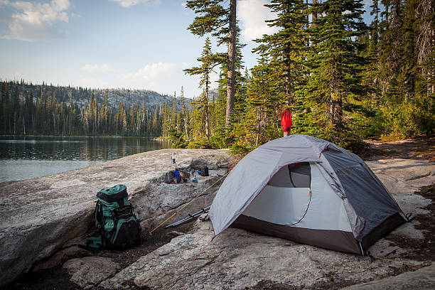Tent pitched alongside a mountain lake. stock photo