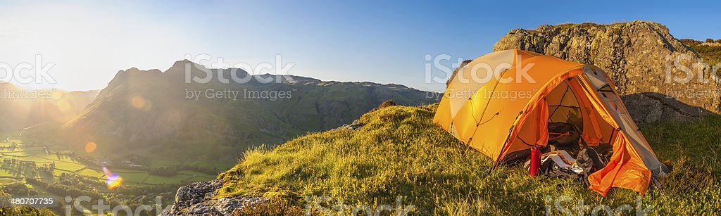 Tent pitched on idyllic mountaintop overlooking summer valley sunset panorama stock photo