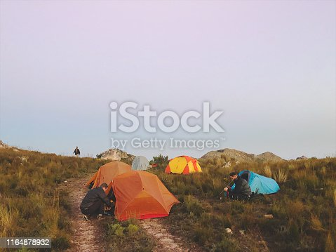 A group of tents on top of a mountain in the wilderness with hikers gathering breakfast and making coffee above Stellenbosch Cape Town South Africa