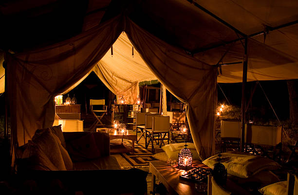 Tented safari camp by night A luxury tented safari lamp lit by torches at night entertainment tent stock pictures, royalty-free photos & images