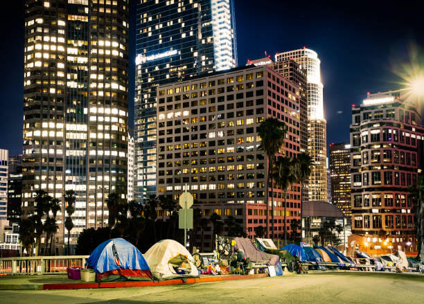 Tents beside skyscrapers in Los Angeles downtown at night Los Angeles, CA, USA - September 2018:  View of homeless people tents near the highway in LA Downtown with skyscrapers. homelessness stock pictures, royalty-free photos & images