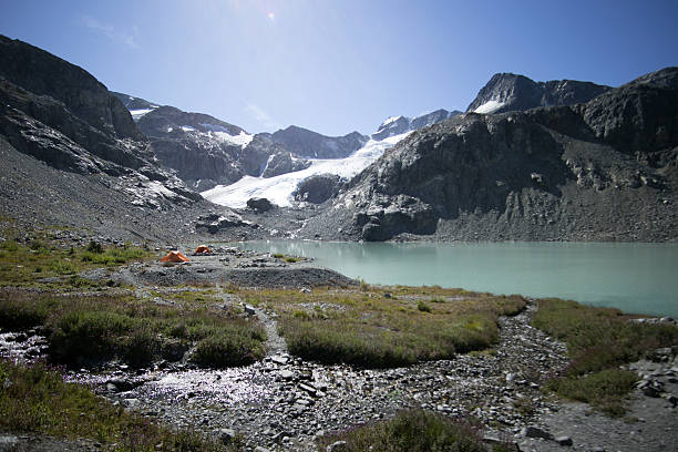 Tents pitched by a glacier lake stock photo