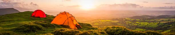 Tents wild camping on mountain overlooking idyllic valley sunset panorama stock photo