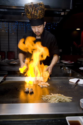 Head chef at Japanese steakhouse at work in Tepan Grill as part of dining entertainment; focus on shrimp and base of flames; copy space