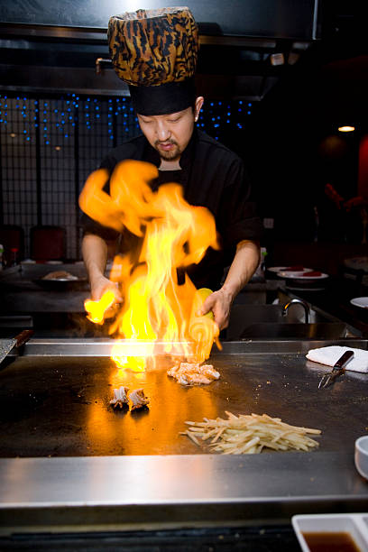 Tepan Grill Ablaze (XXL) Head chef at Japanese steakhouse at work in Tepan Grill as part of dining entertainment; focus on shrimp and base of flames; copy space ablaze stock pictures, royalty-free photos & images