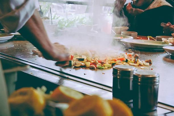 teppanyaki-restaurant: koch kochen vor gäste - teppan yaki grill stock-fotos und bilder