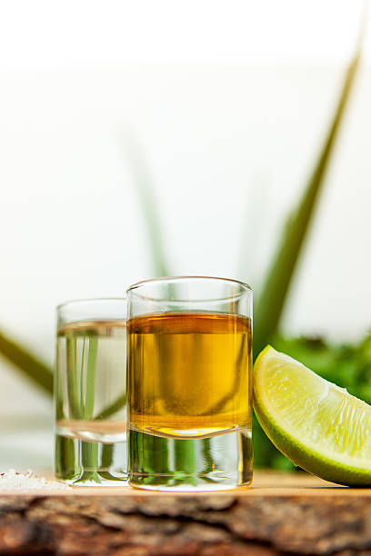 Tequila Tequila shots with lime and corse salt on raw edge wooden board. tequila shot stock pictures, royalty-free photos & images
