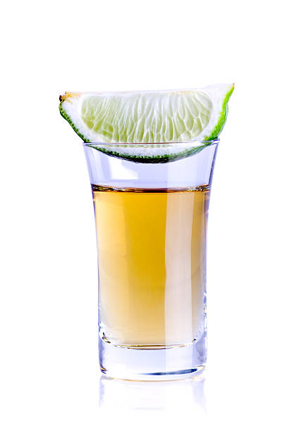 Tequila shot A tequila shot with a slice of lime isolated on pure white. tequila shot stock pictures, royalty-free photos & images